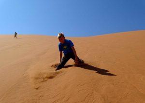 Ein Kind tollt in den Dünen am Sossusvlei in Namibia