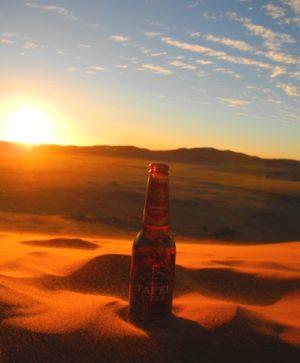 Tafel Lager Bier auf einer Düne im Sonnenuntergang